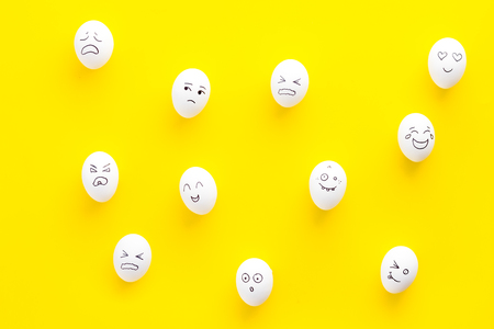 Basic emotions concept. Faces drawn on eggs. Happy, smile, sad, angry, in love. Yellow background top view pattern Stock Photo