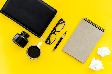 retro and modern writer desktop with coffee, notebook and ink on yellow table background top view mock up