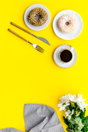 holiday lunch for woman with cup of americano, donut and flowers on yellow background top view mock up