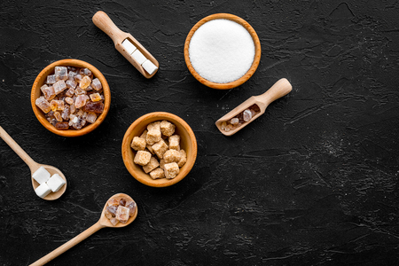 Brown and white sugar in bowls, scoop and spoon. Cane, refind, granulated, cubes, candy. Black background top view copy space Stock Photo
