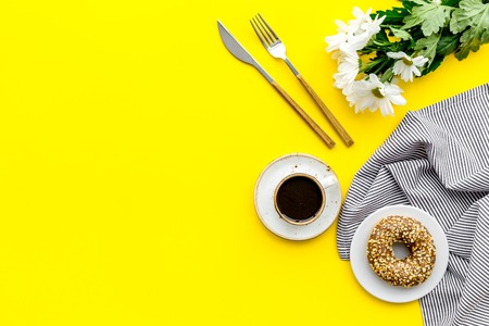 Breakfast with coffee, donuts and flowers on yellow table background top view mockup