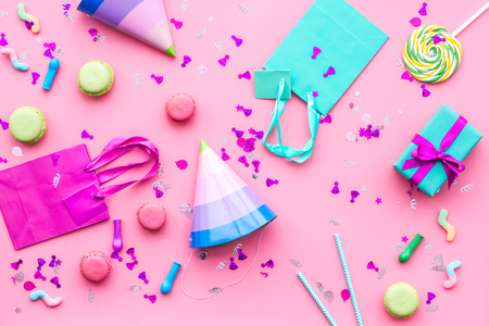 Birthday party accessories. Party hat, sweets, paper bag for gift on pink background top view copy space pattern. Reklamní fotografie