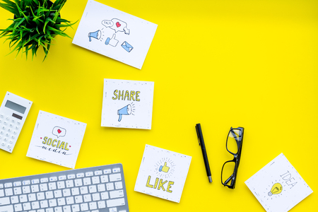 Social media icons on work desk of marketing expert. Digital promotion of goods and services. Yellow background top view.