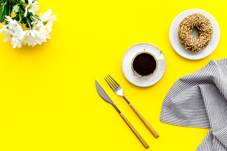 Woman desk with flowers, coffee and donuts for breakfast in spring design on yellow background flat lay mock-up Stock Photo