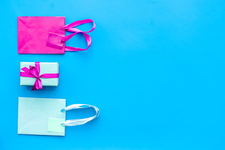 Gift box and colorful paper bag on blue background top view mock-up.