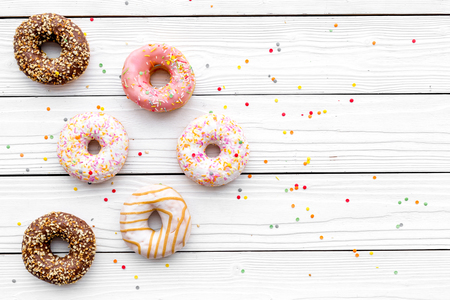 Donuts decorated icing and sprinkles on white background top view space for text