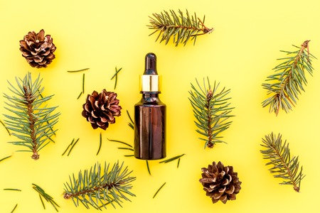 Pine essential oil in bottles on yellow background top view copy space. Pattern with pine branch and cone. 스톡 콘텐츠