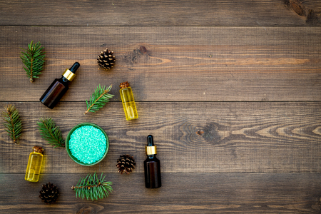 Pine spa cosmetics, products for skin care. Fir essential oil and green aromatic spa salt near branches and cones on wooden background top view.