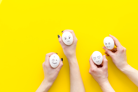 Basic emotions concept. Faces drawn on eggs. Yellow background top view.