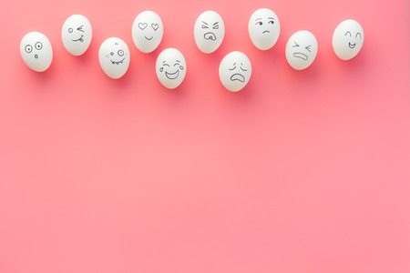 Emotions in communication at social media. Faces drawn on eggs. Pink background top view