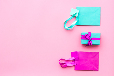 Gift box and colorful paper bag on pink background top view mock-up