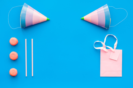 Birthday party accessories. Party hat, sweets, paper bag for gift on blue background top view copy space Reklamní fotografie