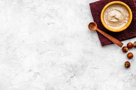Homemade spa with organic scrub and hazelnut on stone background top view space for text
