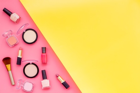Women desk with decorative cosmetics for make up on pink and yellow background flat lay space for text. 写真素材