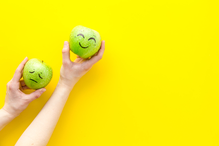 Emotion management concept. Happy and Sad. Face drawn on apple. Yellow background top view.
