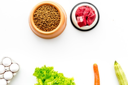 Dry pet food with natural ingredients. Raw meat, vegetables zucchini and carrot near eggs on white background top view.