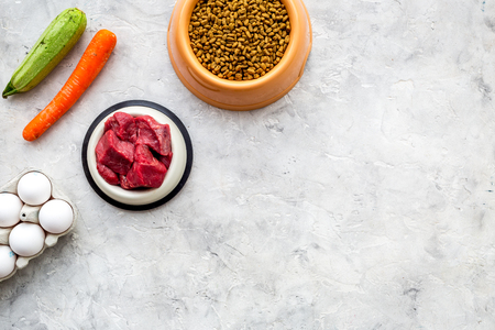 Dry pet food with natural ingredients. Raw meat, vegetables zucchini and carrot near eggs on stone table background top view.