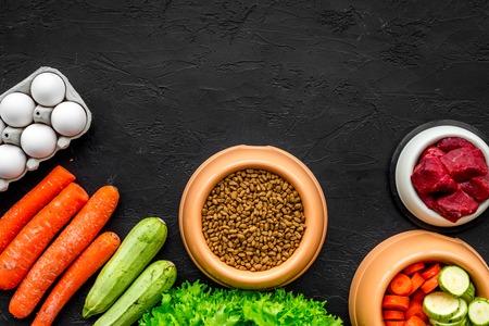 텍스트에 대 한 검은 책상 배경 평면도 공간에 플라스틱 그릇에 개 또는 고양이를위한 건조 식품, 야채와 생고기 애완 동물 관리