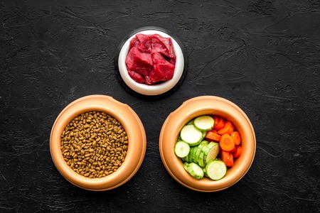 Dry pet food with natural ingredients. Raw meat, vegetables zucchini and carrot on black table background top view mockup. Stok Fotoğraf