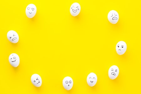 Emotions in communication at social media. Faces drawn on eggs. Happy, smile, sad, angry, in love, saticfied, laughing. Yellow background top view copy space Stock Photo