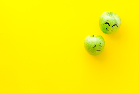 Emotion management concept. Happy and Sad. Face drawn on apple. Yellow background top view copy space Stock Photo
