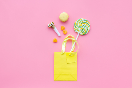 Gift concept. Sweets, paper bag for gift on pink background top view mock up