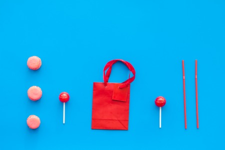 Gift concept. Sweets, paper bag for gift on blue background top view mock up