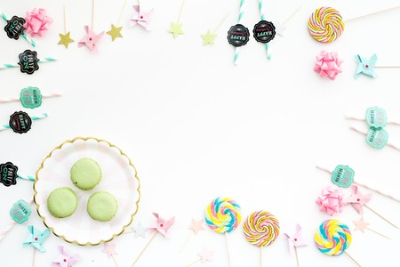 Sweets for party background. Macarons and lollipop on white top view copy space
