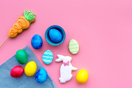 Easter celebration with colorful eggs and gingerbread in shape of easter bunny and carrot. Pink background top view mock up