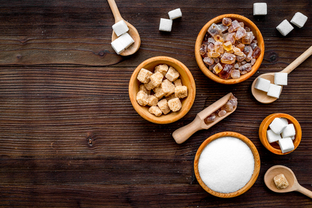 Sugar types. Cane, refind, granulated, cubes, candy sugar. Dark wooden background top view copy space Stock Photo