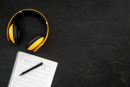 Work space of composer or dj with headphones and notes black background top view mock-up