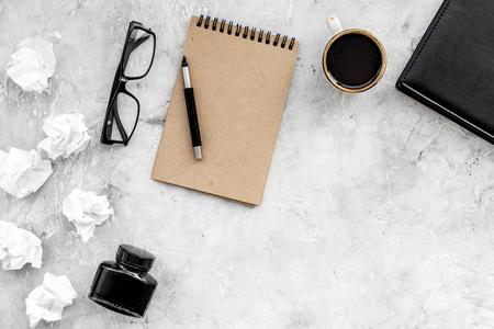 Notizbuch, Tinte, Badfeder, Kaffee, Gläser für Verfasserarbeitsplatz stellten auf graues Draufsichtmodell des Steinschreibtischhintergrundes ein Standard-Bild - 97834607