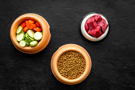 Dry pet food with natural ingredients. Raw meat, cut vegetables zucchini and carrot on black backgroud top view mockup Banco de Imagens