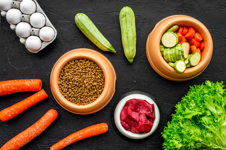 Dry pet food with natural ingredients. Raw meat, vegetables zucchini and carrot near eggs on black backgroud top view pattern