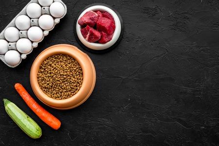 텍스트 검은 배경 상위 뷰 공간에 플라스틱 그릇에 개 또는 고양이를위한 건조 식품, 야채와 생고기 애완 동물 관리
