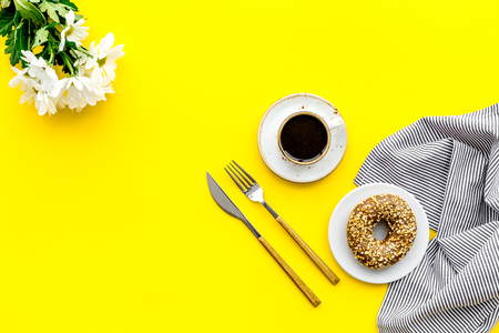 modern breakfast desing with sweet donut, coffee and flowers on woman yellow desk background top view mock up