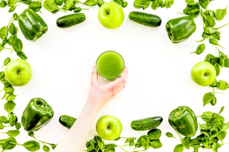 Greeny vegetable smoothie in glass with cucumber, pepper, apple, celeriac on white background top view mock up