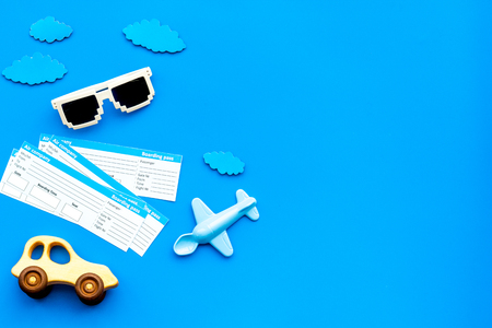 Sample of airplane ticket. Family trip with kid. Airplane, car toys. Blue background flat lay space for text. Stock Photo
