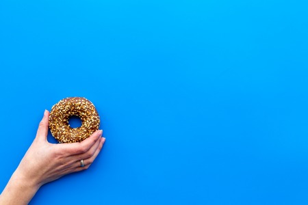 Sweet tasty snack. Glazed donut on blue table background top view copy space
