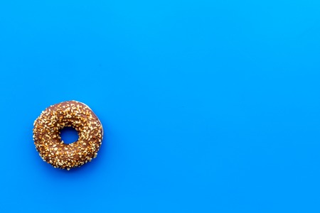 Glazed donut for dessert on blue background flat lay mock up.