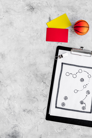 Sport judging concept. Basketball referee. Tactic plan for game, basketball ball, red and yellow cards, whistle on stone background top view copy space Stock Photo