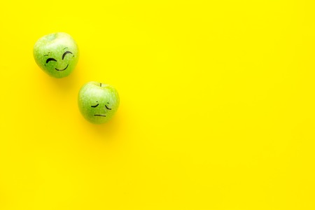 Basic emotions concept. Faces drawn on apples. Happy, smile, sad, angry, in love. Yellow background top view copy space Stock Photo