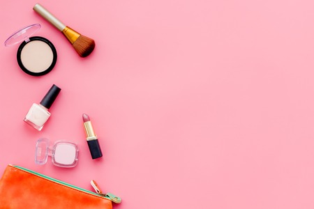 Decorative cosmetics for make up on pink desk background top view mock up