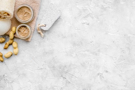 Homemade spa with organic scrub and peanut on stone background top view space for text
