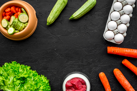 Dry pet food with natural ingredients. Raw meat, vegetables zucchini and carrot, eggs on black table background top view mock-up. Reklamní fotografie