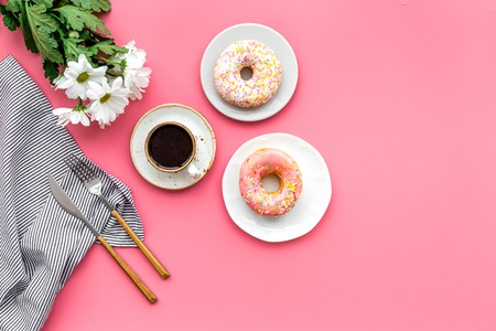 Modern breakfast design with sweet donut, cup of coffee and flowers on woman pink desk background top view mock up