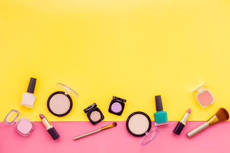 Women desk with decorative cosmetics for make up on pink and yellow background flat lay space for text. Archivio Fotografico