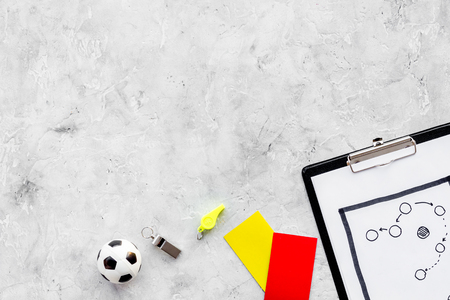 Sport judging concept. Soccer referee. Tactic plan for game, football ball, red and yellow cards, whistle on stone background top view,
