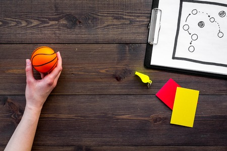 Sport judging concept. Basketball referee. Tactic plan for game, basketball ball, red and yellow cards, whistle on wooden background top view,