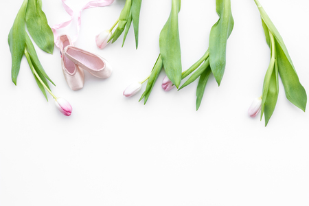 Ballet shoes near delicate flowers on white background top view copy space